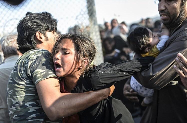 Penaberên Sûriyeyî ji deriyê sînor ê Kaniya Xezalan a Rihayê ê derbasî Serxetê bûn. Ji şerê Sûriyeyê yê navxweyî mîlyonek û 800 hezar penaber xwe spastine Tirkiye û bajarên Bakurê Kurdistanê. [Bülent Kılıç, AFP/Getty]