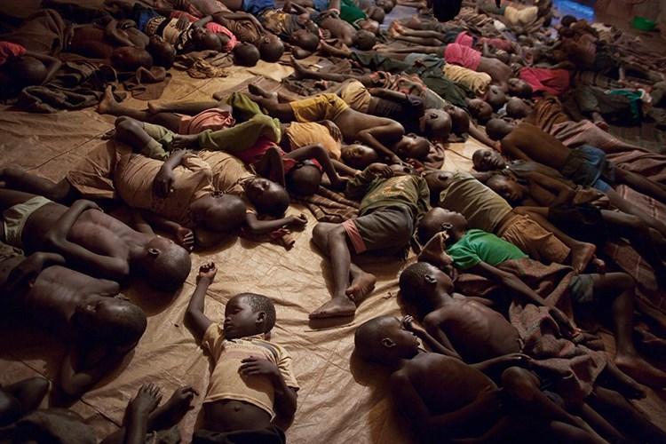 Zarokên ku ji hezên ku serî hildan reviyan, li stargeheke Guluya Ugandayê radizin. [John Stanmeyer, National Geographic Creative]