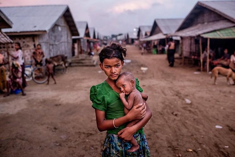 Rohîngyayiyên misilman li Sîttweyê ji ber zilm û zordariyê malen xwe terikandibûn û reviyabûn. Myanmar jî  ji bo wan  baregehek avakir. Di baregehê de keçikeke birayê xwe yê ku birçî ye hildigire. Piraniya Rohingyayinên ku ji welatê xwe reviyan, koç kirine Malezyayê. [Tomas Munita, The New York Times/Redux]