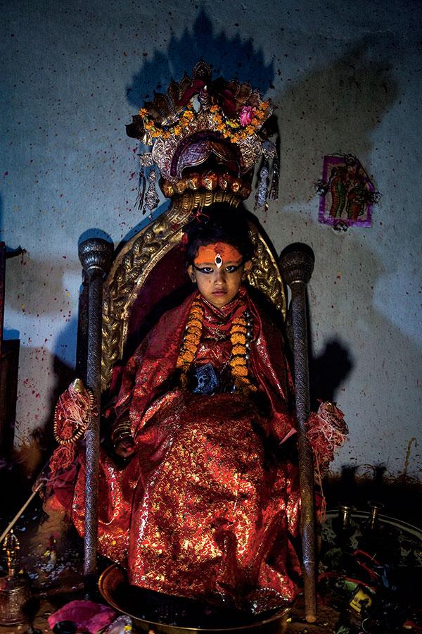 Unika Vajracharyaya şeş salî wekî kumariya Patan, di roja ewil de piyên xwe daniye ser sîniya servîsê. Marekî yezdanî jî serê wê diparêze. [Wêne: Stephanie Sinclair]