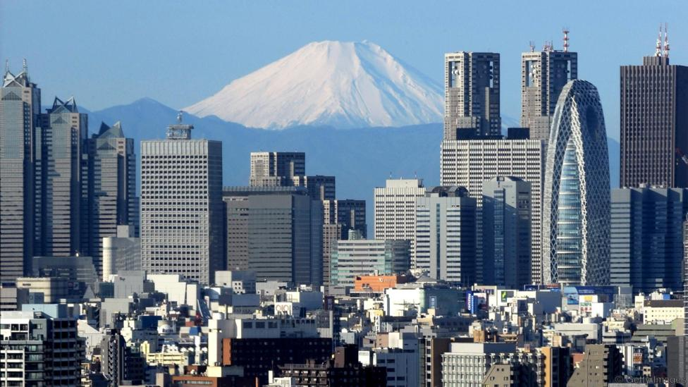 TO GO WITH AFP STORY 'Lifestyle-Asia-cities-Tokyo,FEATURE' by Frank Zeller (FILES) This file picture taken on January 4, 2011 shows Japan's Mt. Fuji rising behind Tokyo's Shinjuku area. On a satellite image of the Earth at night, there is no brighter spot. Greater Tokyo, home to an astonishing 35 million people, is by far the biggest urban area on the planet. AFP PHOTO / FILES / KAZUHIRO NOGI (Photo credit should read KAZUHIRO NOGI/AFP/Getty Images)