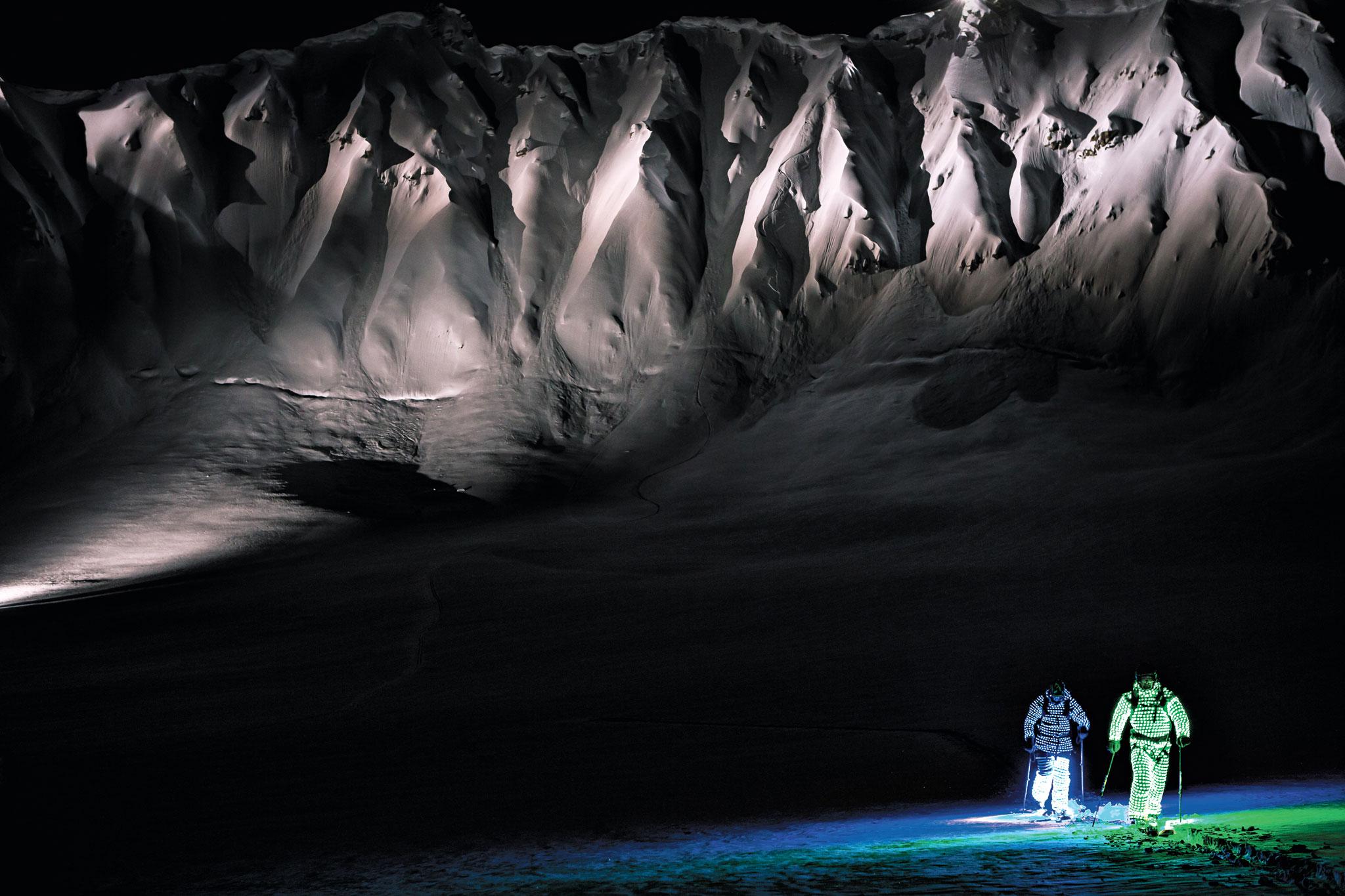 Chris Benchetler û Daron Rahlves, bi cilên xwe yên ku bi tîrêjên LEDê hatine xemilandin li Anchorageya nêzî Alaskayê şev ronî dikirin.